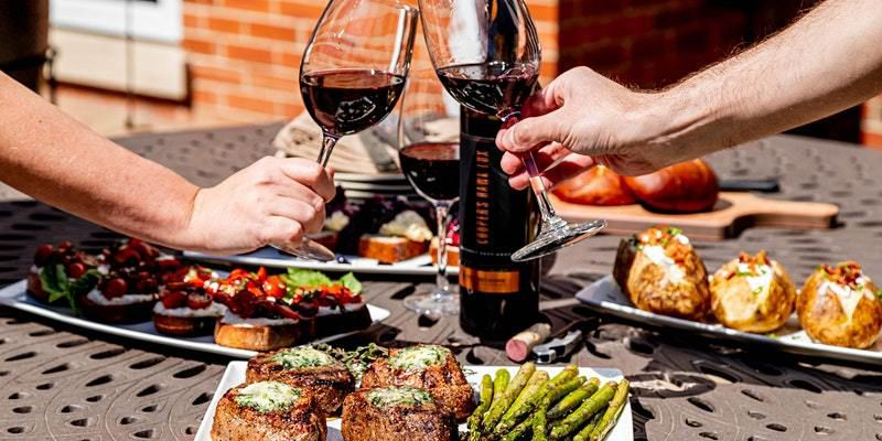 Two people toasting with glasses of wine over a table full of food.