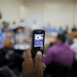 In this Aug. 20, 2012 photo, a prison guard records a video with a cell phone during an appeal hearing for U.S. citizen Jason Sachary Puracal in Granada, Nicaragua.  As a three-judge appellate panel mulls the 35-year-old American's fate, the case has drawn the scrutiny of U.S. lawmakers and human-rights advocates, including the California Innocence Project, which works to absolve people who have been wrongfully convicted. In late 2010 masked policemen raided his seafront real estate office and took him to Nicaragua's maximum security prison. Prosecutors charged that Puracal was using his business as a front for money laundering in a region used to transport cocaine from Colombia to the United States. Because no drugs or cash were seized, Puracal's family and friends thought he wouldn't be held long, but nine months later, a judge convicted Puracal and sentenced him to 22 years in prison.