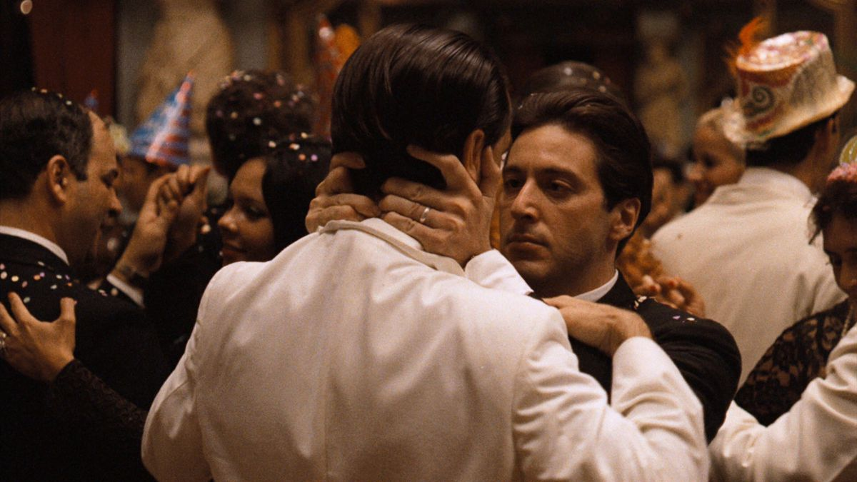 Michael Corleone embraces another man in a threatening manner at a New Years party in The Godfather Part II.