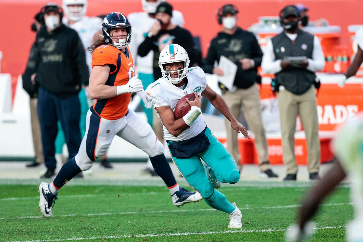 Miami Dolphins quarterback Tua Tagovailoa (1) runs the ball in the third quarter against the Denver Broncos at Empower Field at Mile High.