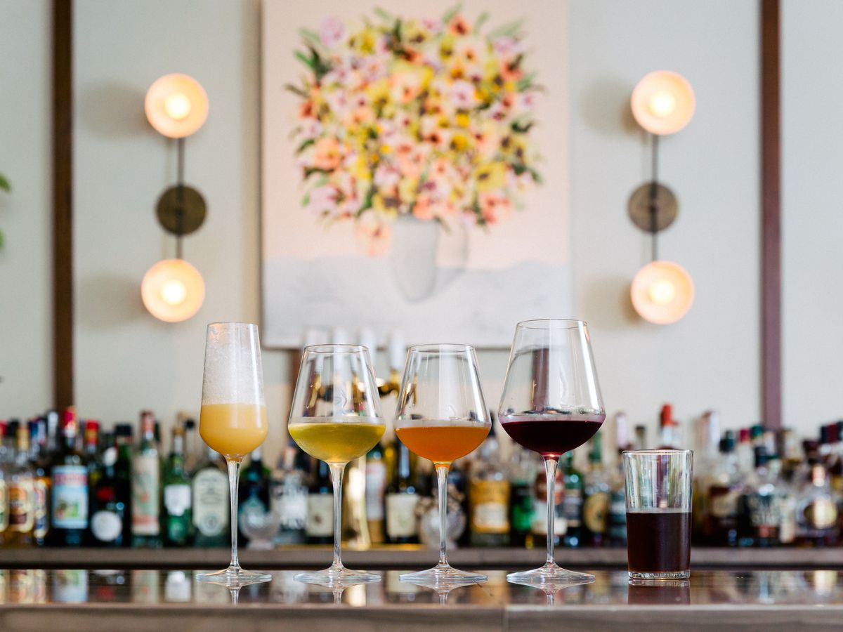 Four stemmed glasses sit on top of a bar.
