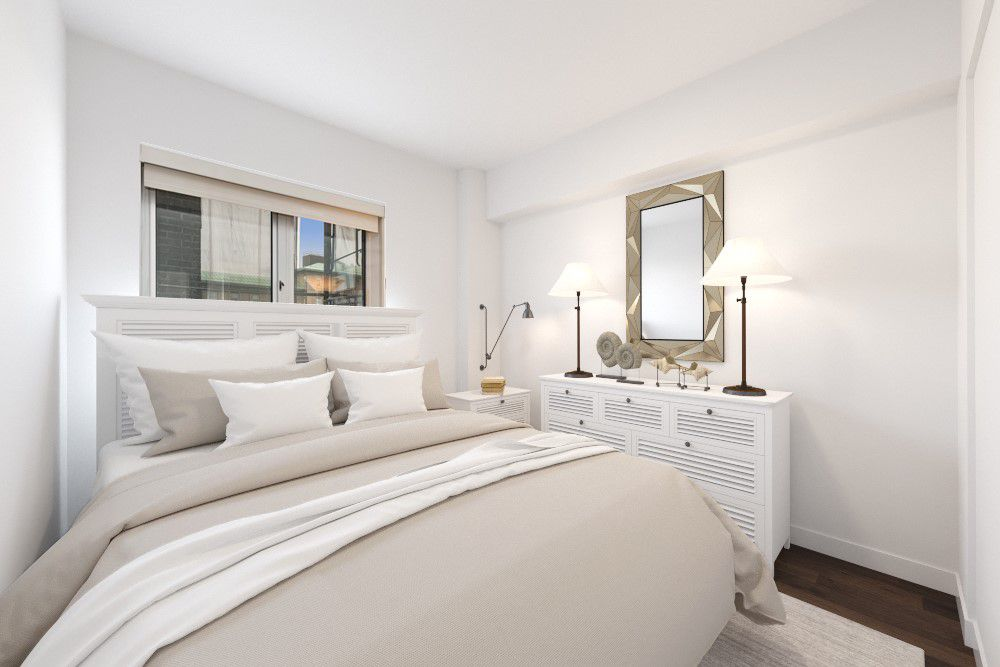 A bedroom with a large bed, a window, hardwood floors, and white walls.