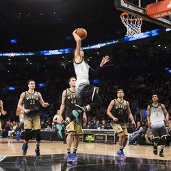 United States' Zach LaVine dunks in front of World players during the second half of the NBA Rising Stars Challenge basketball game in Toronto on Friday, Feb. 12, 2016. Jazzmen Trey Lyles (41) and Raul Neto (25) look on for the World team on the play.
