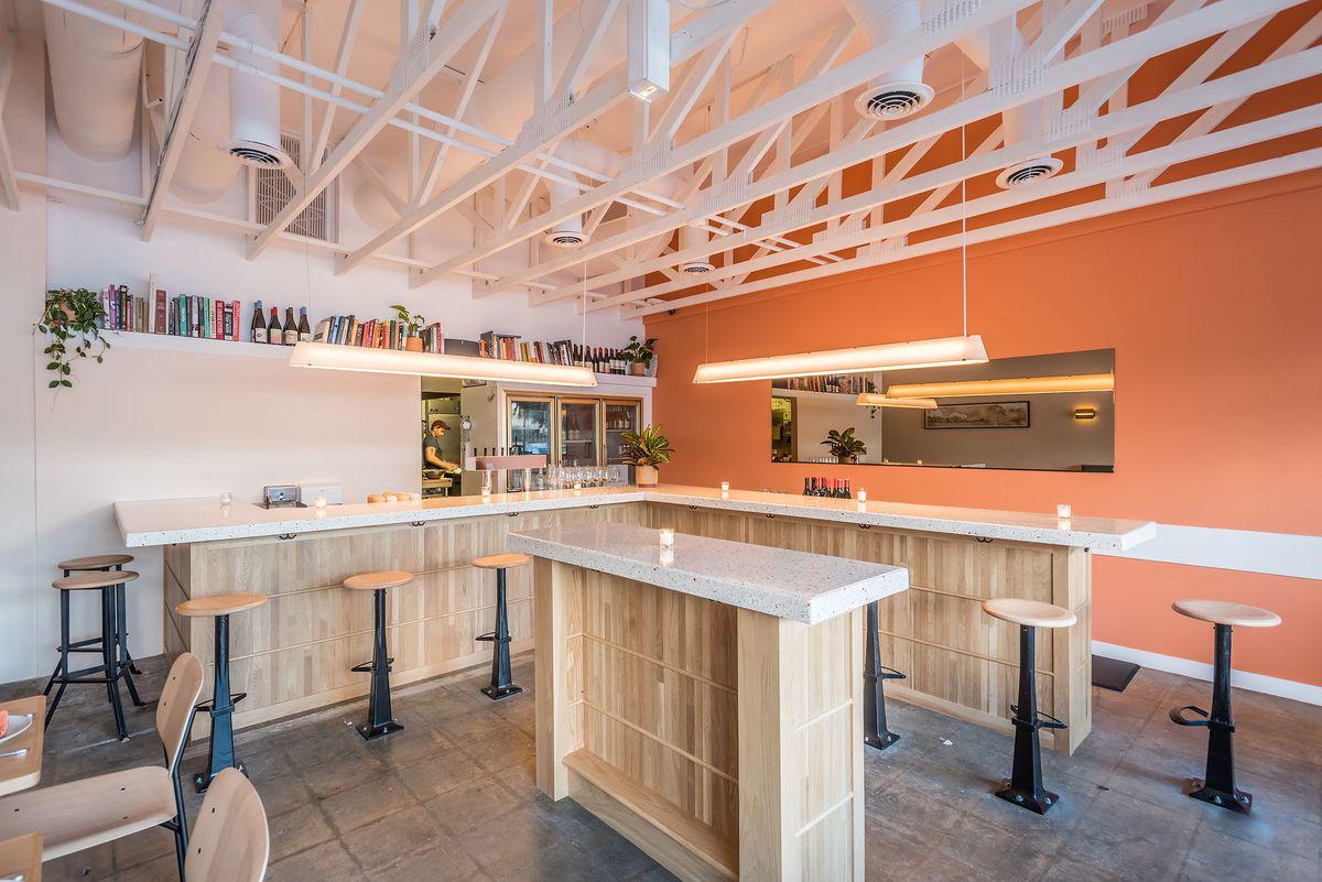 A terrazzo bar and tall ceiling'd restaurant.
