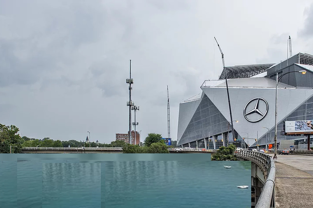 a poorly photoshopped image of Mercedes-Benz Stadium towering over a large body of water.