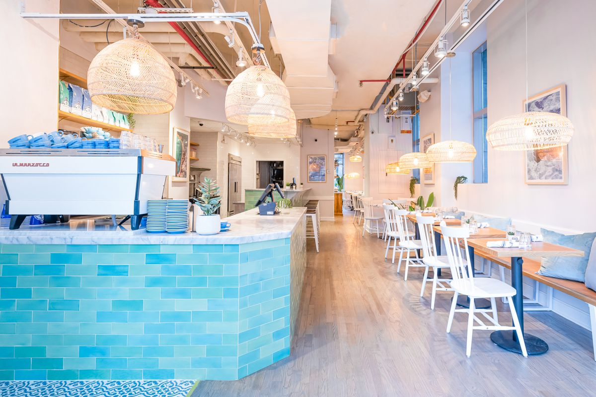 The interior of a coffee shop with white chairs and tables to the right and a baby blue coffee counter to the left