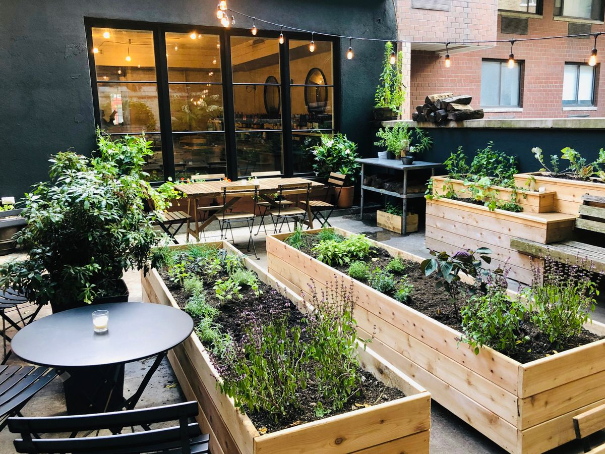 An outdoor seating area with several wooden tables and chairs, planters with greens growing out of them, and a windowed storefront visible in the background
