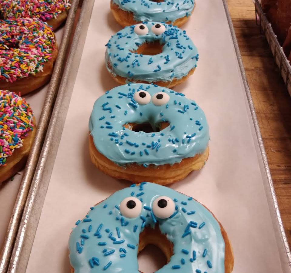 A line of doughnuts are on tissue paper on a metal tray. They're all decorated like Cookie Monster, with light blue frosting, blue sprinkles, and eyes.