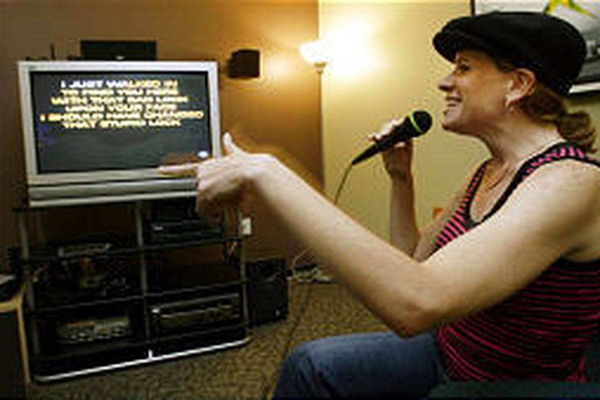 Maureen Farley demonstrates the new karaoke feature of Microsoft Corp.'s Xbox video gaming system.