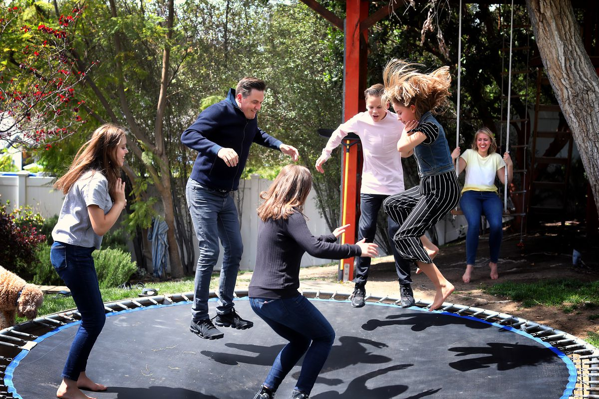 """Eve McKeown, 16, along with Greg, 43, Grace 18, Jack, 15, and Esther, 12, jump on the trampoline while Anna McKeon watches from a swing in Calabasas, California,on Saturday, May 1, 2021. Greg McKeown's latest book, """"Effortless,"""" came out last week."""