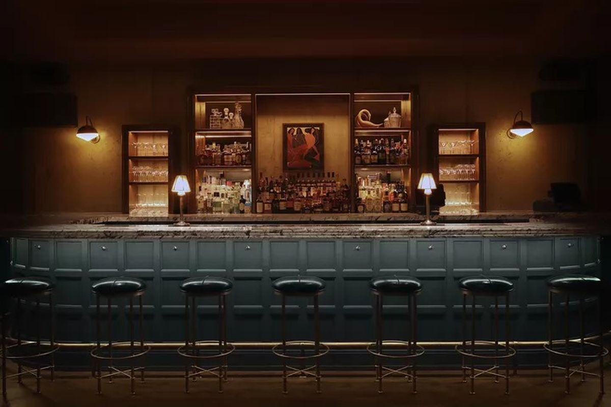 Lazy Bird's dimly lit bar area features lamp lighting, stools for sitting, and shelves lined with glasses and liquor bottles.