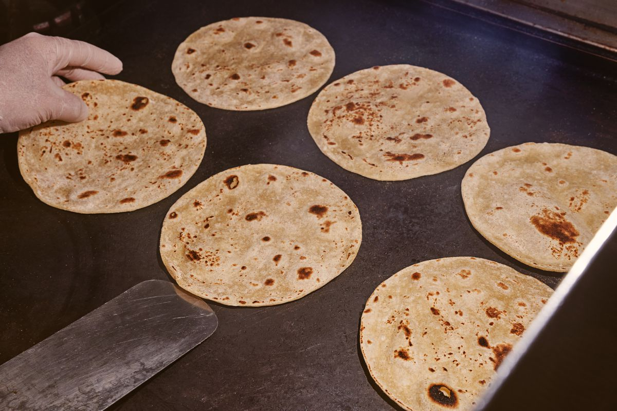 A gloved hand lifts a flour tortilla from a griddle using a metal spatula