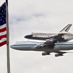 Hitching a ride on top a special NASA Boeing 747 jet, the space shuttle Discovery soars past Capitol Hill in Washington, Tuesday, April 17, 2012, after a flight from Cape Canaveral, Fla. Discovery, the world's most traveled spaceship, now becomes an attraction at the Smithsonian's National Air and Space Museum's Stephen F. Udvar-Hazy Center in Chantilly, Va., next to Dulles International Airport.