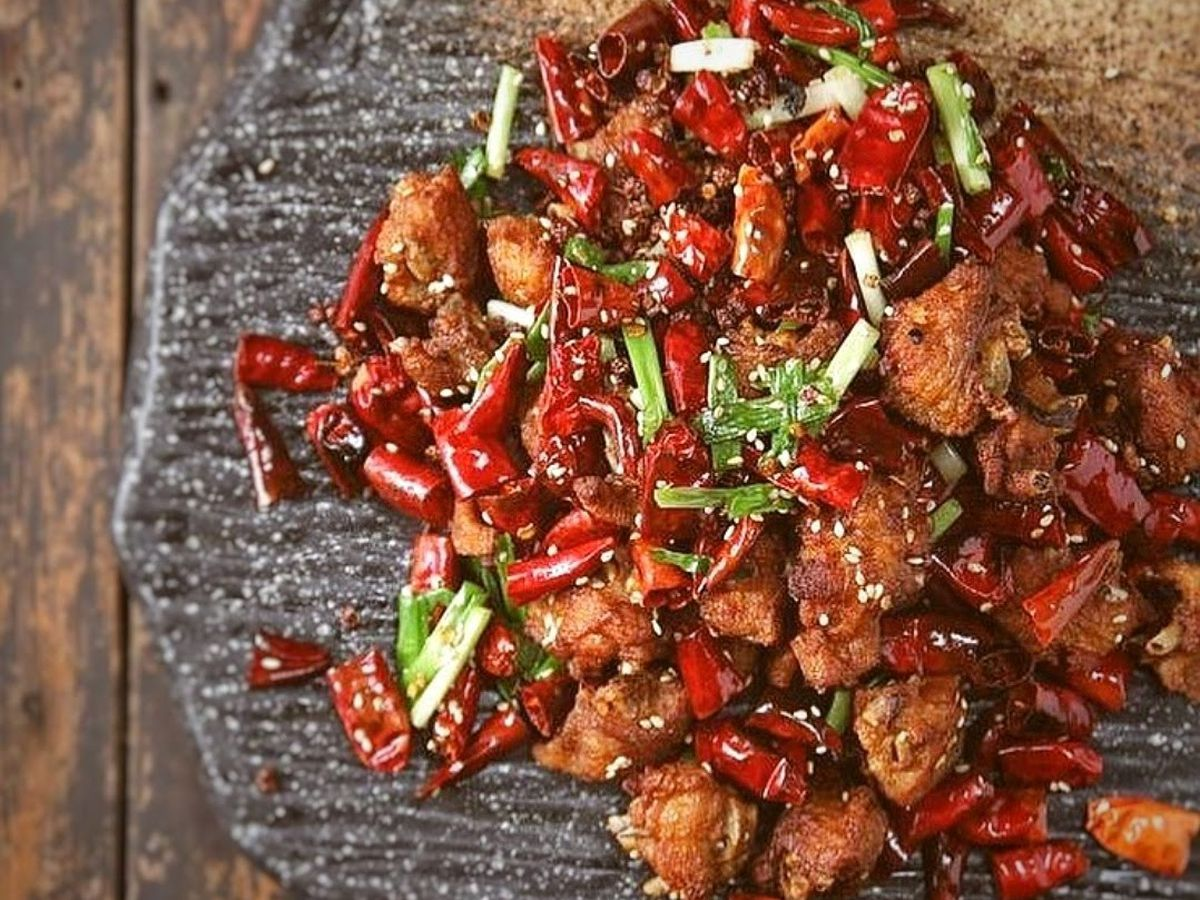 Chunks of fried chicken are seen mixed with chopped peppers