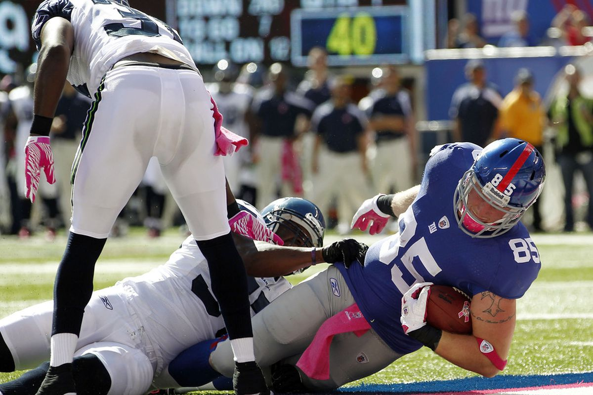 Jake Ballard of the New York Giants dives in for a touchdown in front of David Hawthorne of the Seattle Seahawks  at MetLife Stadium on October 9, 2011 in East Rutherford, New Jersey.  (Photo by Jeff Zelevansky/Getty Images)