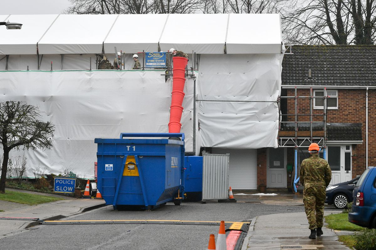 People dressed in British Army fatigues remove bricks and rubble from the Skripal's house in Salisbury, where the roof is being taken down after the nerve agent attack.
