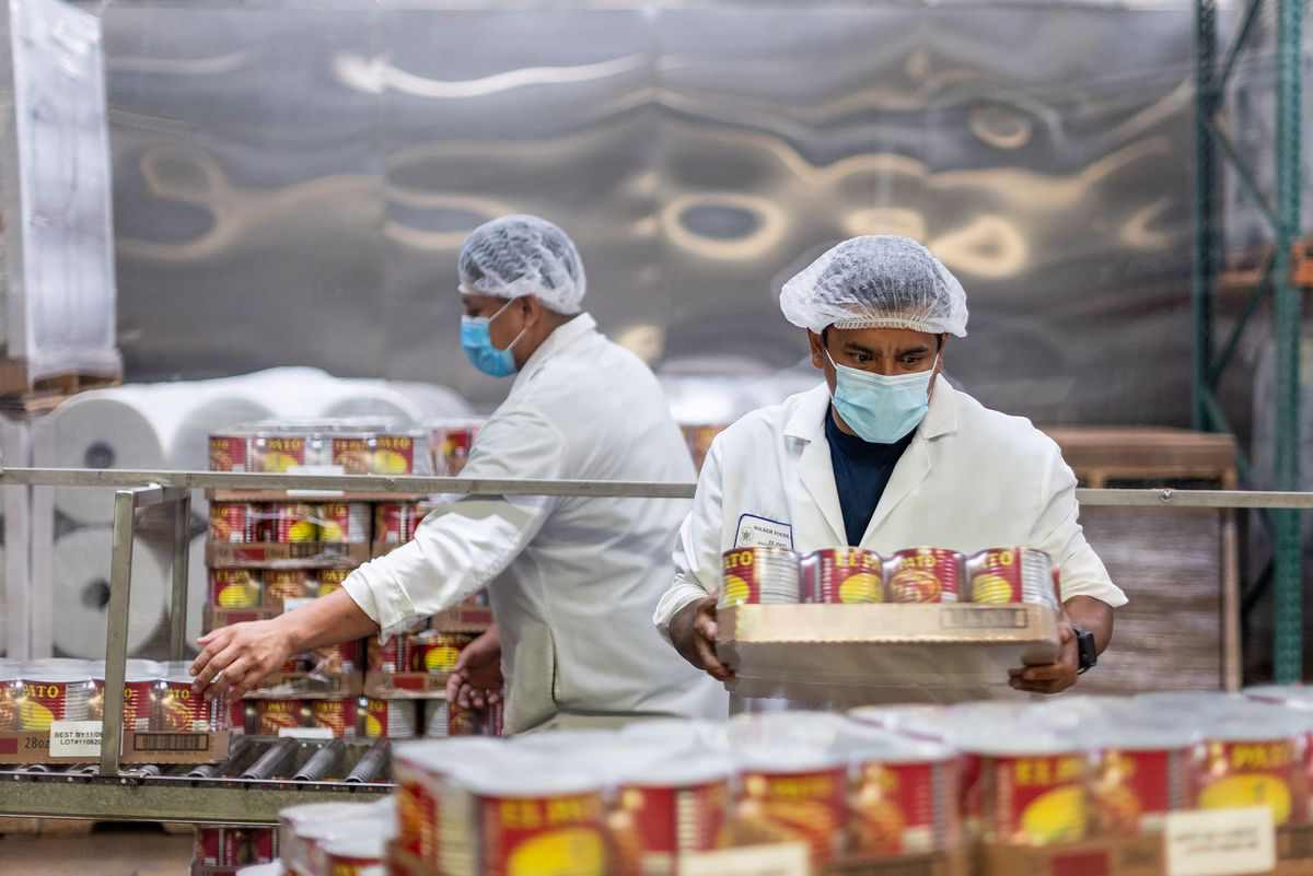 A worker moves tins of red cans of salsa inside of a warehouse.