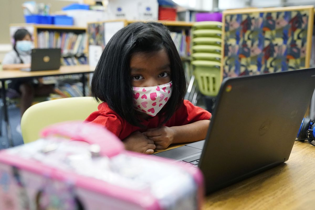 Young girl in a mask printed with pink hearts, works on her laptop at a learning center.