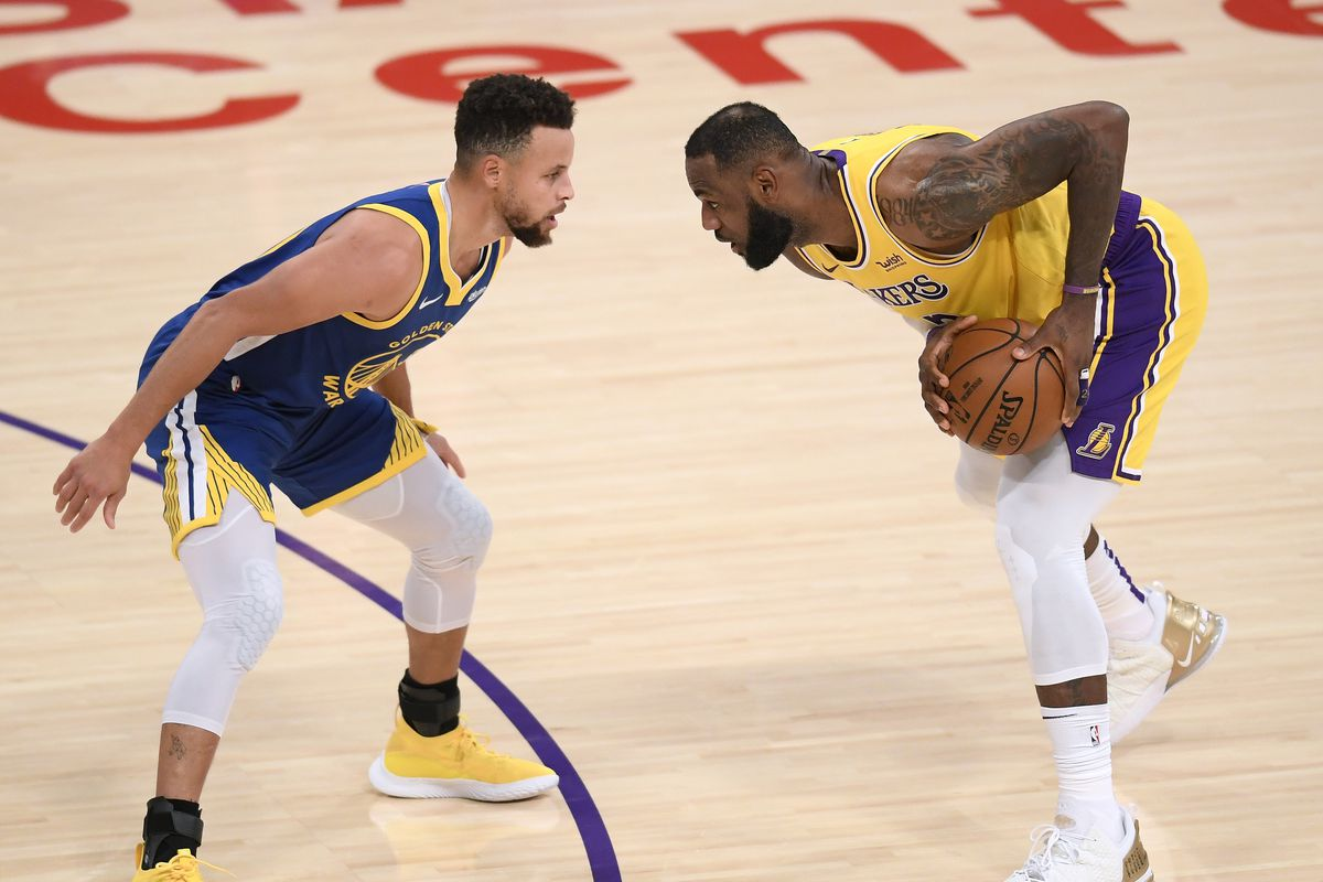 LeBron James of the Los Angeles Lakers is guarded by Stephen Curry of the Golden State Warriors during the first half at Staples Center on January 18, 2021 in Los Angeles, California.