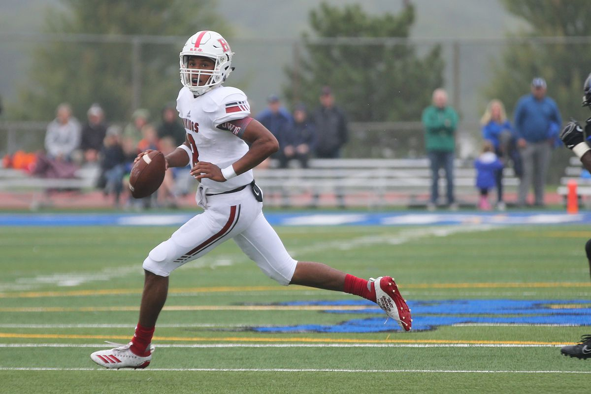 Homewood-Flossmoor's Dominick Jones (8) rolls out to throw a pass against Lincoln-Way East.