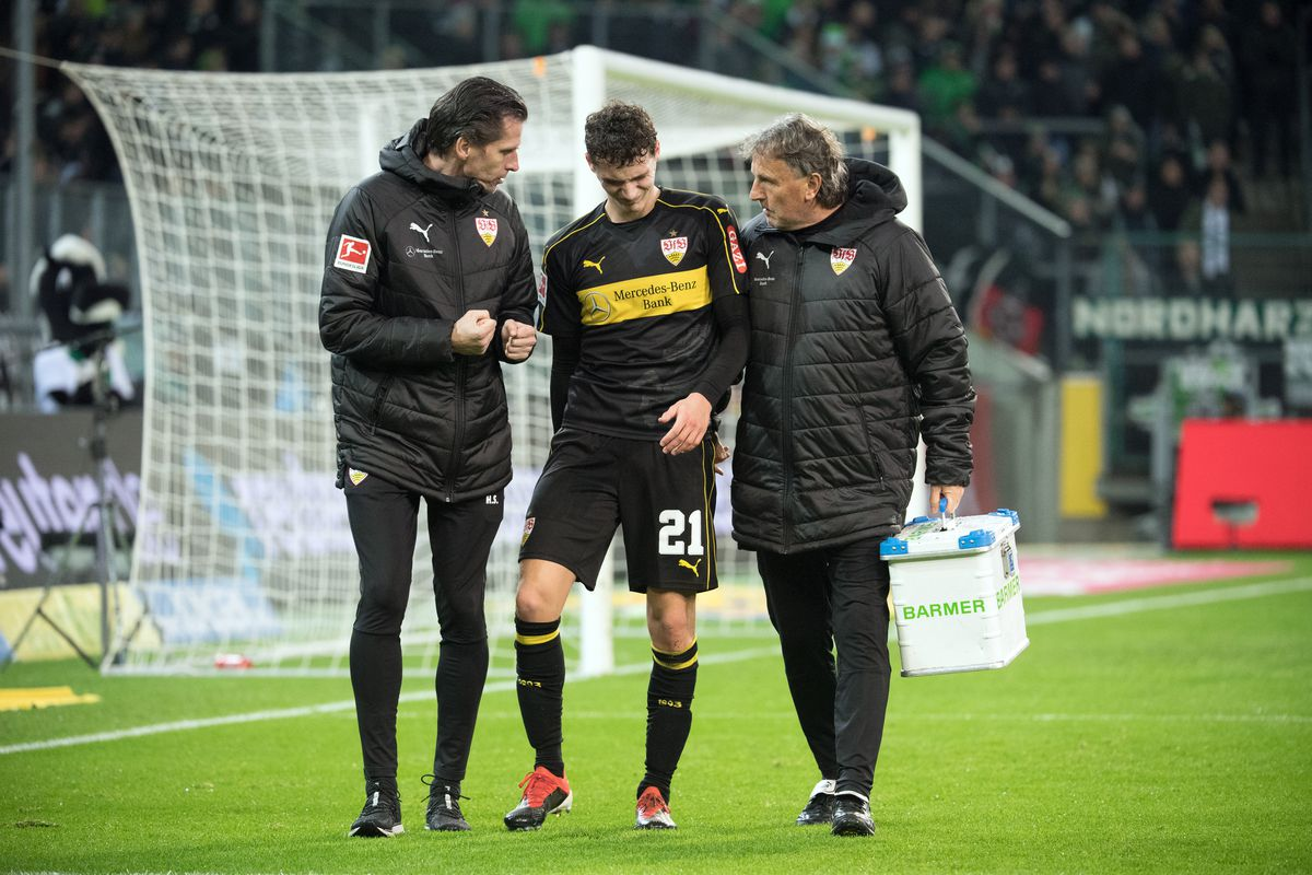 Borussia Mönchengladbach - VfB Stuttgart 09 December 2018, North Rhine-Westphalia, Mönchengladbach: Soccer: Bundesliga, Borussia Mönchengladbach - VfB Stuttgart, 14th matchday in Borussia Park stadium. Stuttgart's Benjamin Pavard (M) is led off the square injured. The 22-year-old scored his own goal to 3-0 to make the debacle perfect. He also injured his thigh during the action in the 84th minute. Photo: Federico Gambarini/dpa - IMPORTANT NOTE: In accordance with the requirements of the DFL Deutsche Fußball Liga or the DFB Deutscher Fußball-Bund, it is prohibited to use or have used photographs taken in the stadium and/or the match in the form of sequence images and/or video-like photo sequences.
