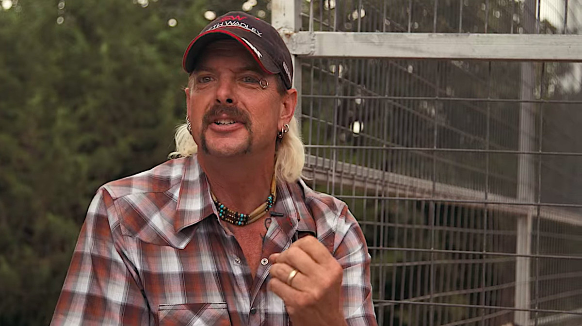Joe Exotic, sitting by a large tiger cage, speaks into the camera in a screenshot from Tiger King.