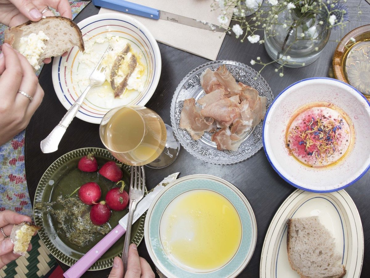 From above, two people eat from a table strewn with dishes, including whole radishes, bread, olive oil, and sliced meat, as well as glasses of wine and a bouquet