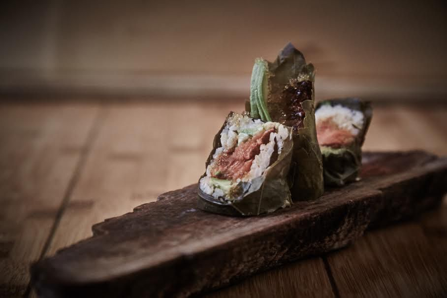 A sushi roll features salmon wrapped in grape leaves