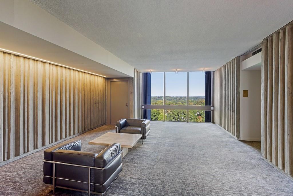 A condo hallway with a big window and concrete walls.