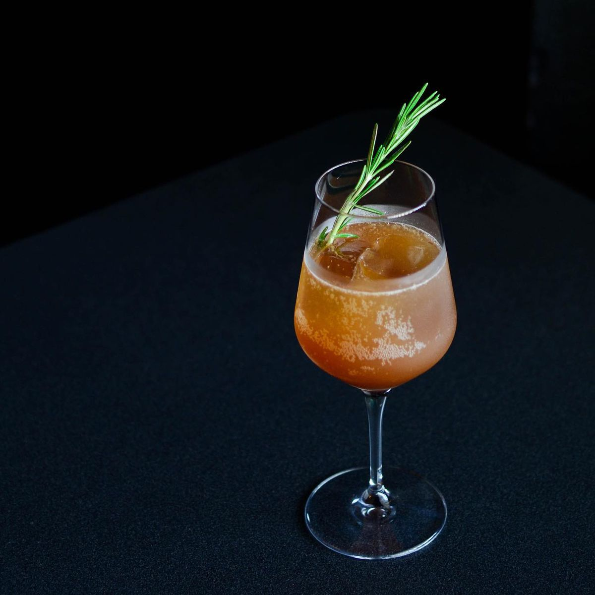 A chilled orange beverage over a big ice cub with a rosemary garnish in a wine glass on a black topped bar