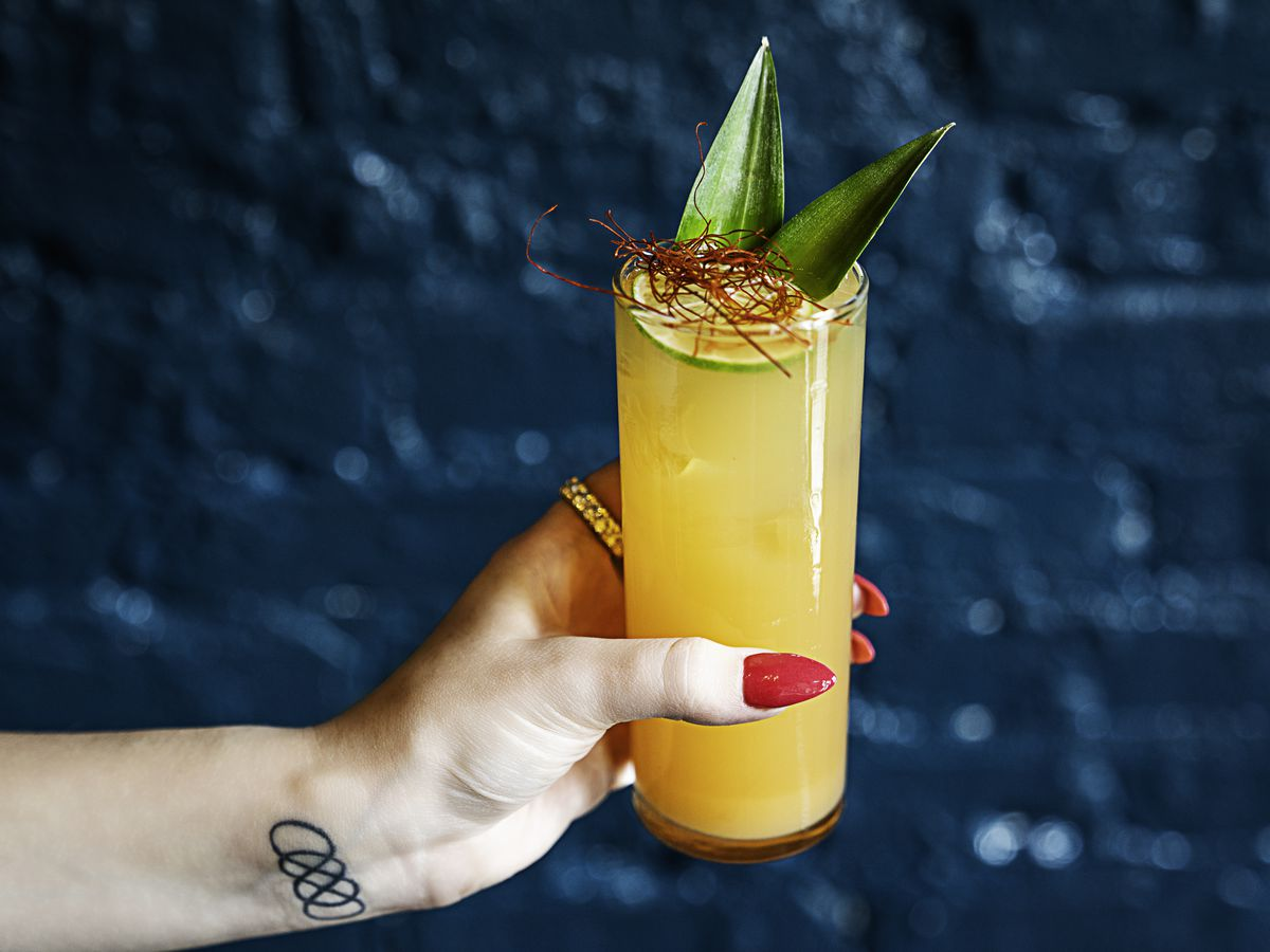 An orange cocktail held by someone with long red nails.