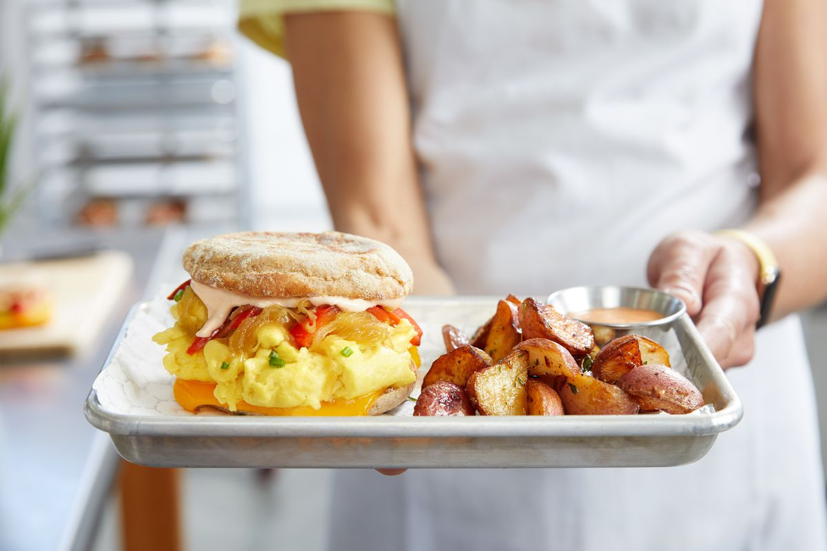 A tray of breakfast food —scrambled egg sandwich and potatoes —held by a server.