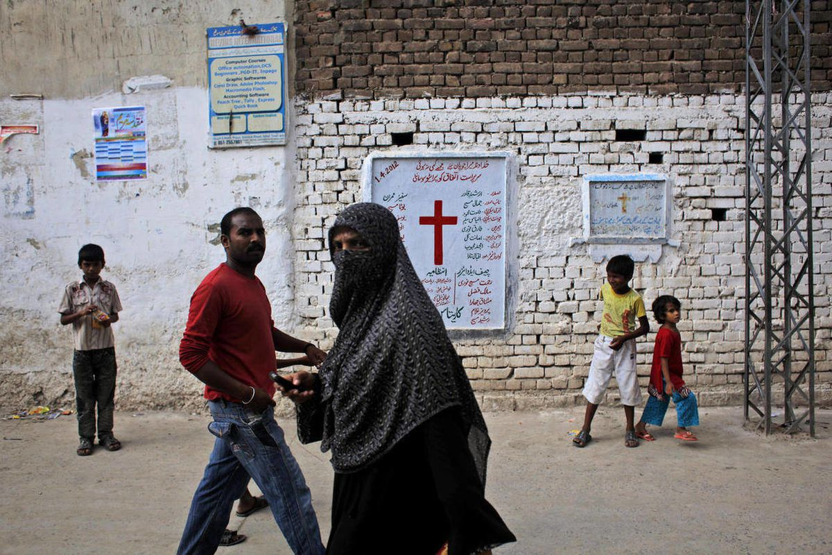 In this Thursday, Aug. 30, 2012, photo, Pakistanis walk in a Christian neighborhood in Islamabad, Pakistan.  The plight of Pakistan's Christian minority has received renewed focus in recent weeks because of the arrest of a young, mentally challenged girl