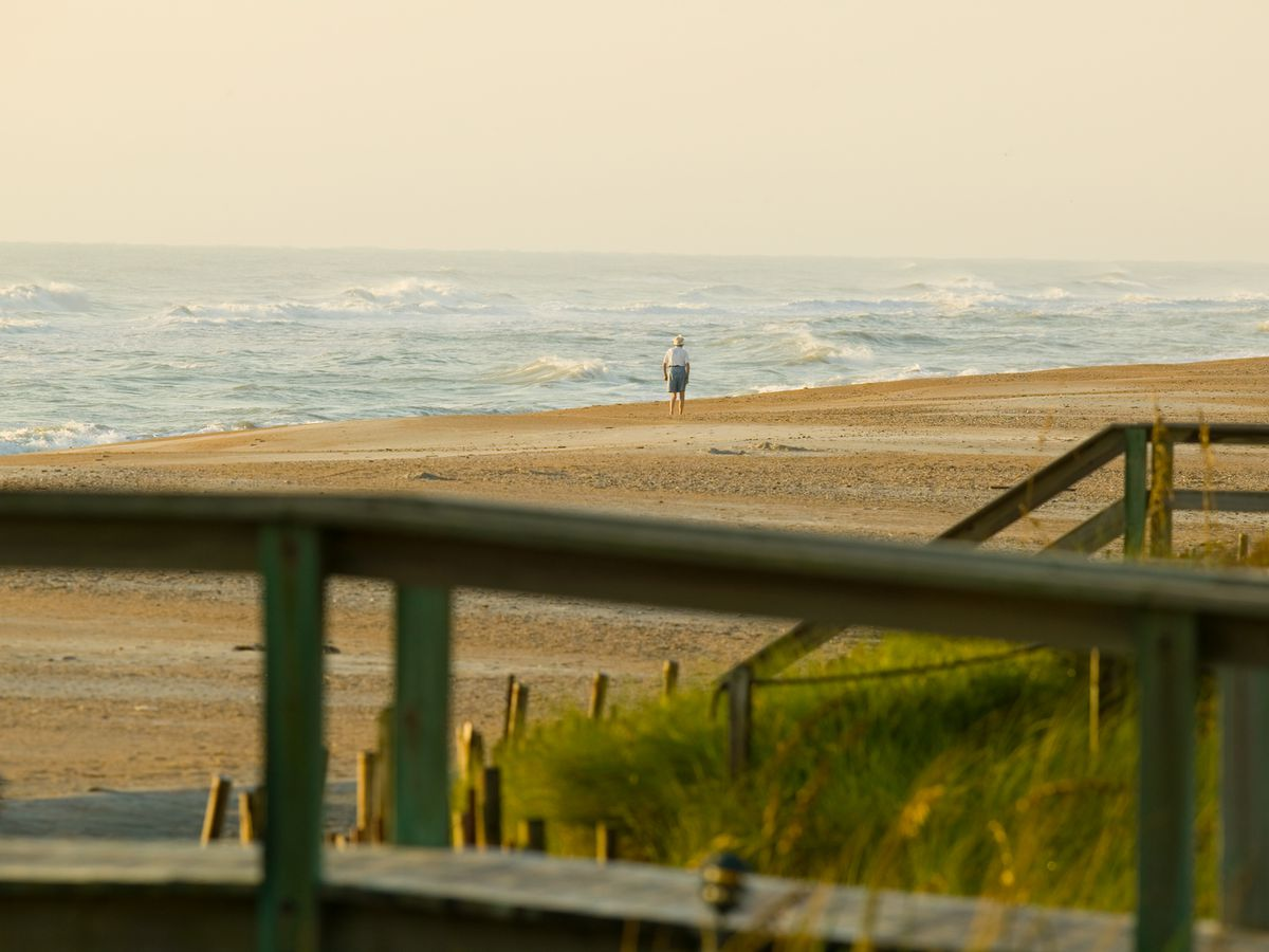 In the foreground is a fence. In the distance is a sandy beach and the ocean.