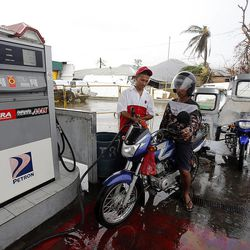 Jadmar Castillo pumps gasoline for Allan Abanas in Tacloban, Friday, Nov. 22, 2013. Some gas stations are reopening following a typhoon.