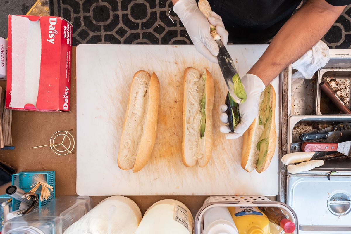 From above, hands press avocado into a sandwich roll.