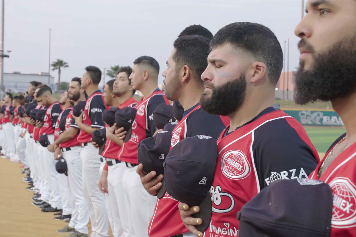 """Members of the Tecolotes de los Dos Laredo, a binational professional baseball team with home stadiums in Nuevo Laredo, Mexico, and Laredo, Texas, stand for the U.S. national anthem before a game in 2019 in Laredo, Texas in a scene from """"Bad Hombres."""""""