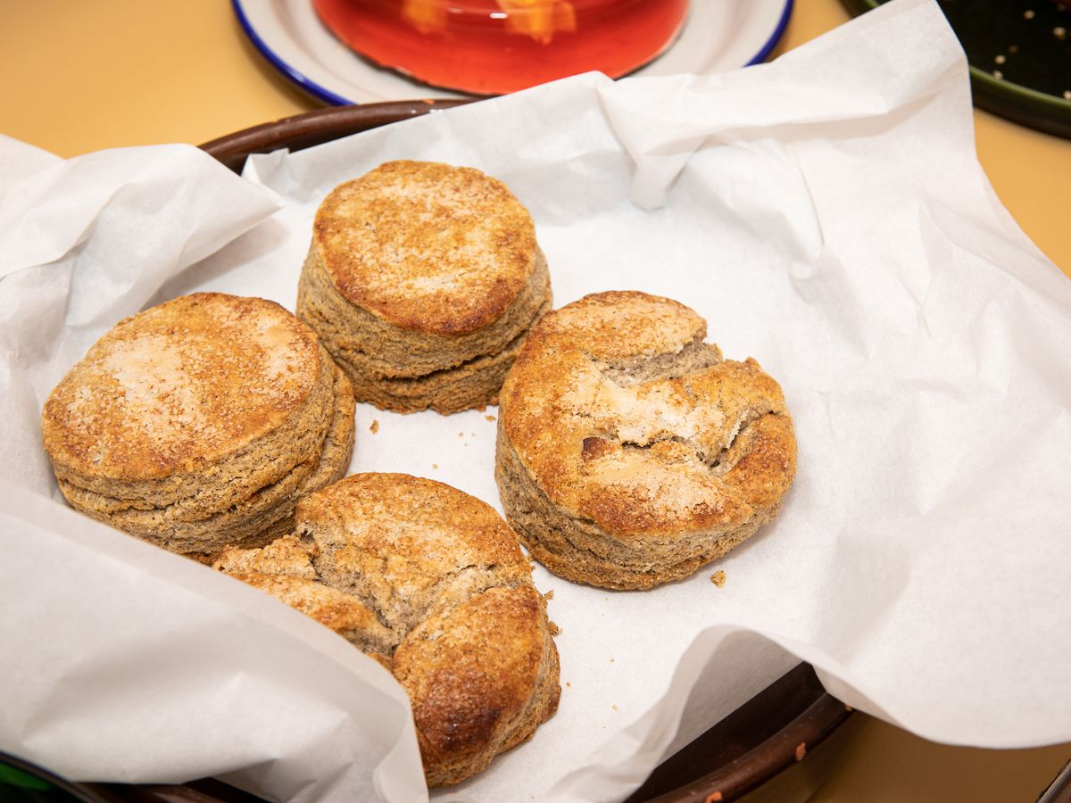 Four brown biscuits arranged in a basket with a white cloth
