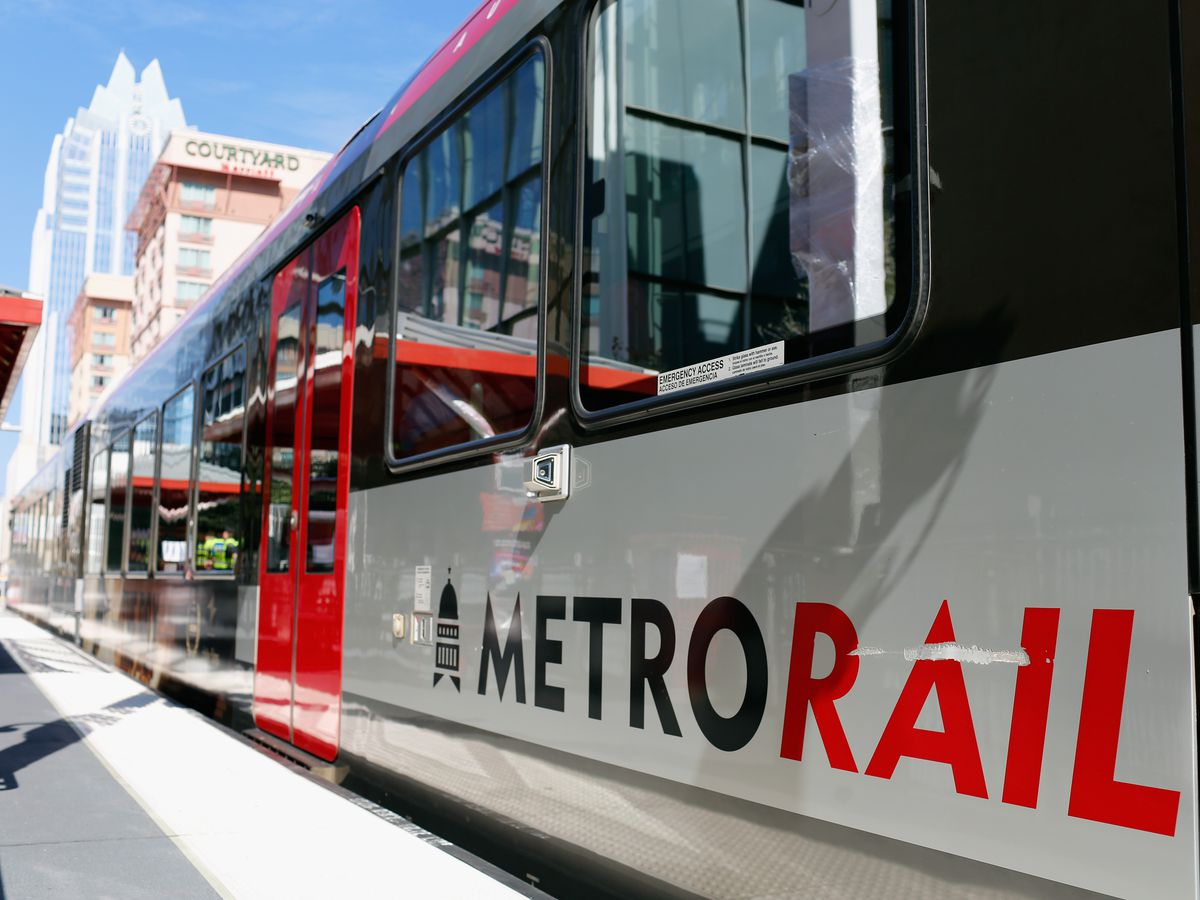 """Low to the ground shot of a modern commuter rail car exterior. It reads """"MetroRail"""" on the side. There are two tall buildings in the background."""