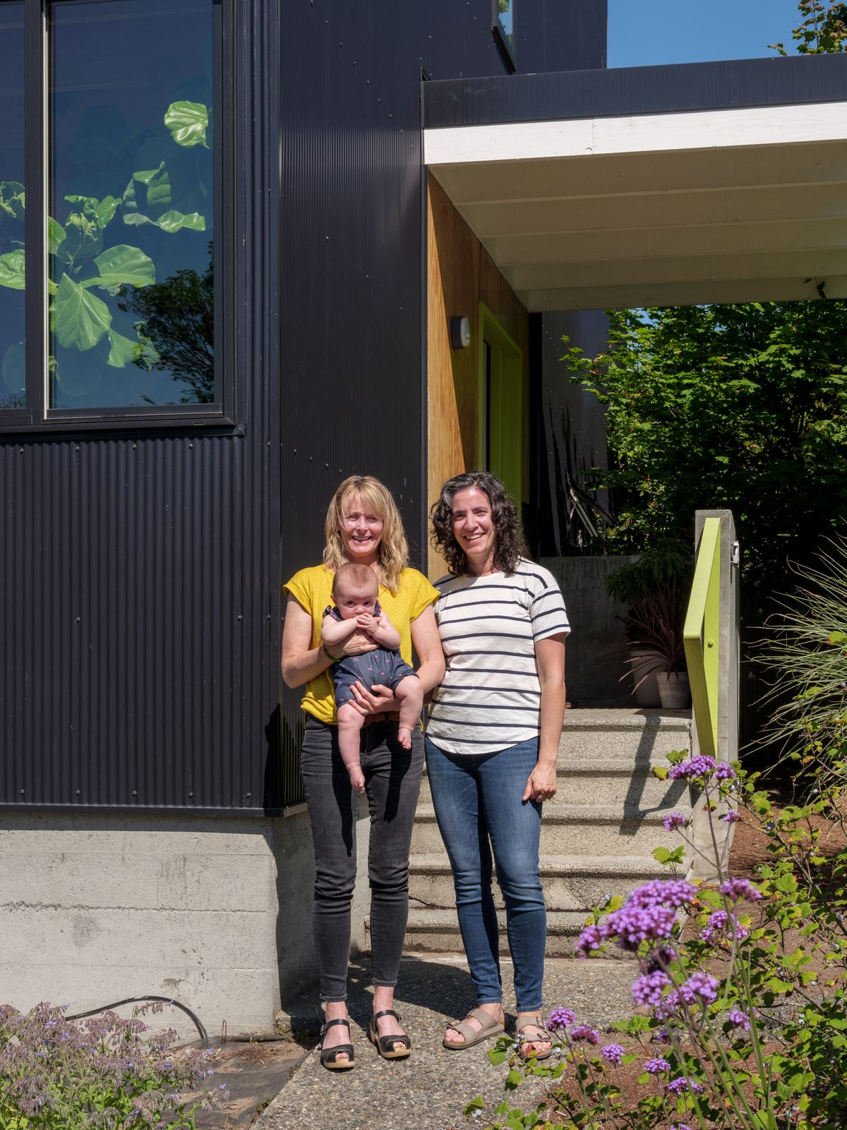 Two women stand next to a house with a painted black facade. One of the women is holding an infant. There are purple wildflowers and plants lining the path they are standing on.