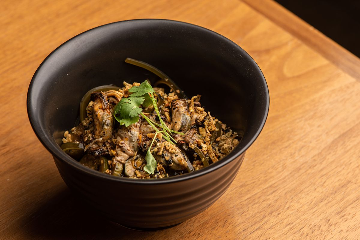 A tall bowl filled with grains and moked mussels on a wooden table.