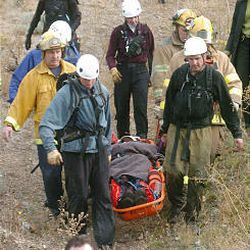 Firefighters and search and rescue workers transport the 65-year-old pilot of the twin-engine plane to a waiting ambulance after the crash Monday near the Point of the Mountain. The pilot and his wife escaped with only minor injuries.