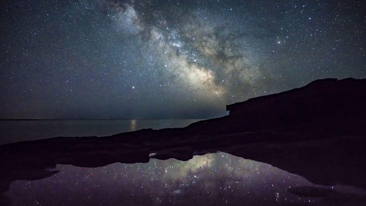 Milky Way and stars shine off the coast of Acadia National Park