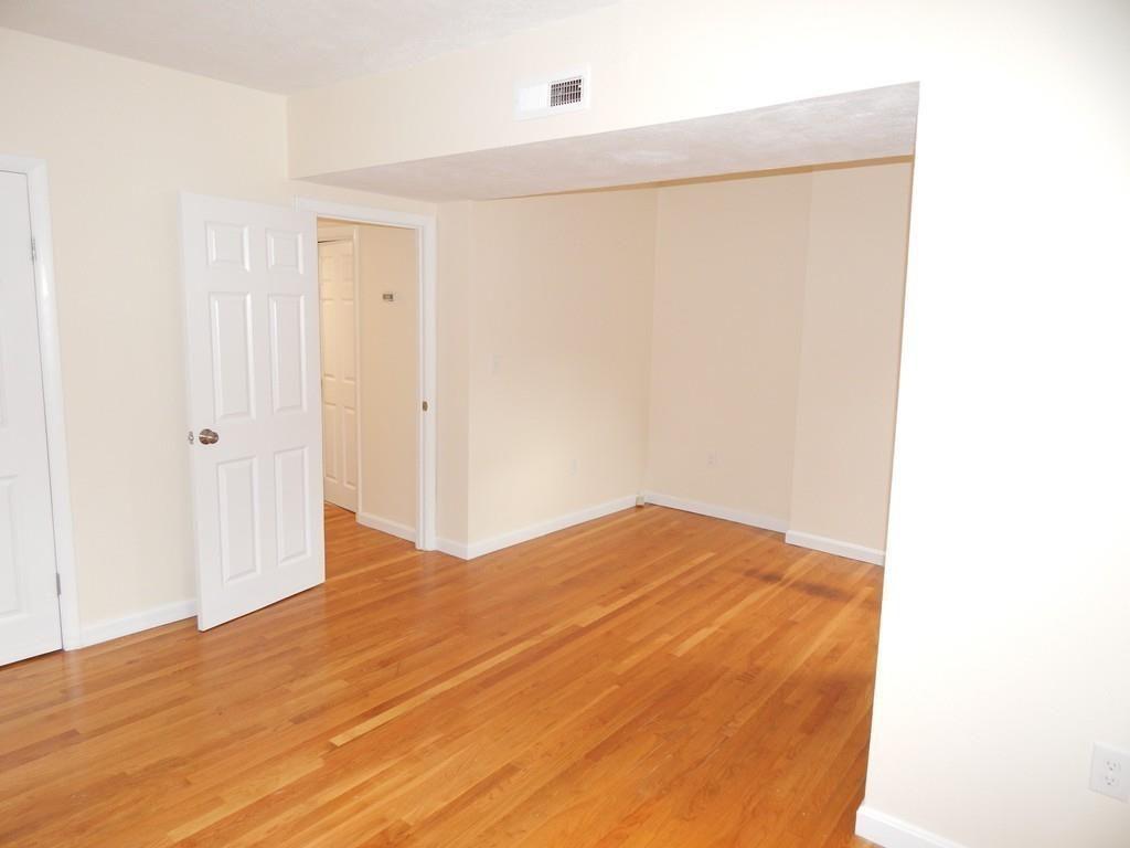 An empty bedroom with hardwood floors and an open door.