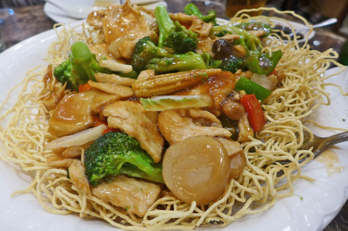 A nest of stiff squiggly noodles with seafood on top.