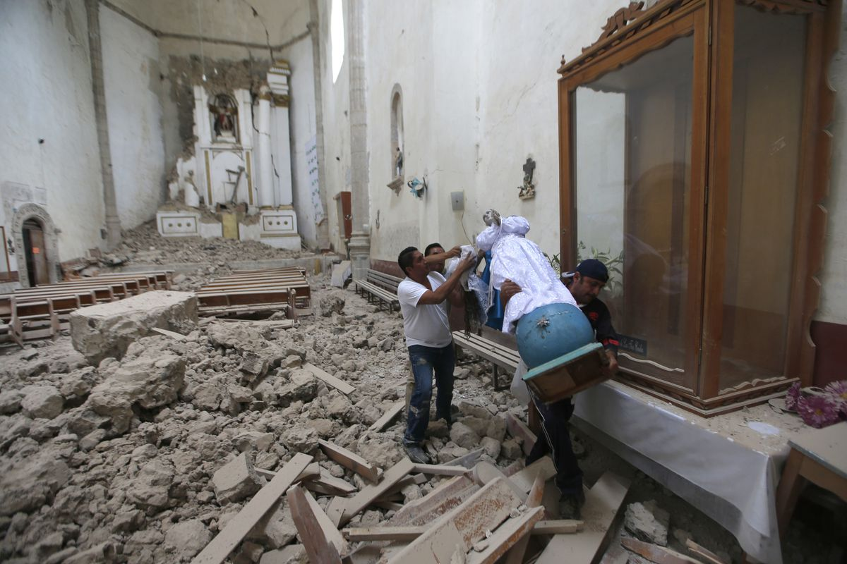 Workers rescue a religious statue from the heavily damaged former convent of San Juan Bautista, in Tlayacapan, Morelos state, Mexico. | Eduardo Verdugo/Associated Press