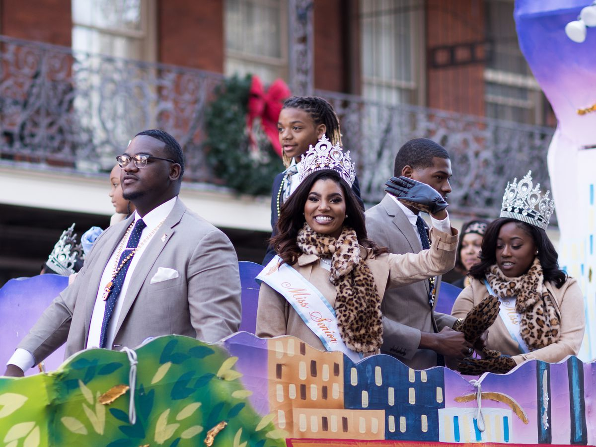 A group of people on a parade float in a parade in New Orleans. The women are wearing elaborate crowns. The parade float has a mural of a city with palm trees on it.