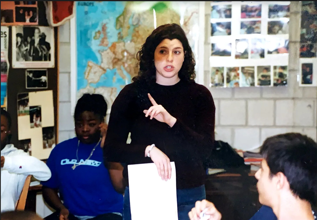 A young woman works in a classroom, pointing as she grasps a piece of paper as students listen around her.
