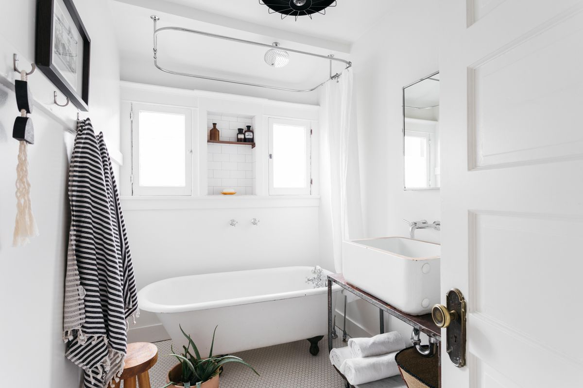 Bathroom with white walls, sink, tile, and claw-foot tub.