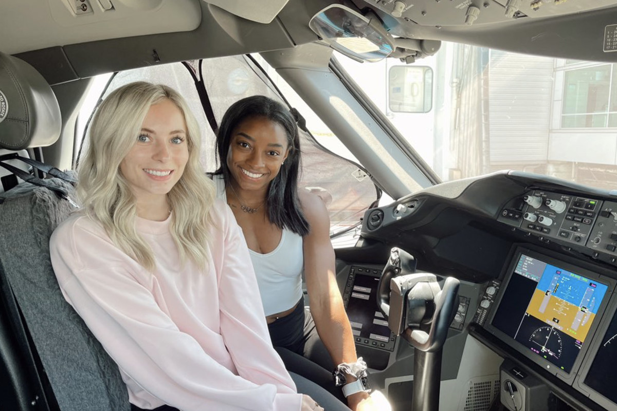 MyKayla Skinner, left, and Simone Biles pose for a photo in the cockpit of their Tokyo, Japan-bound airplane